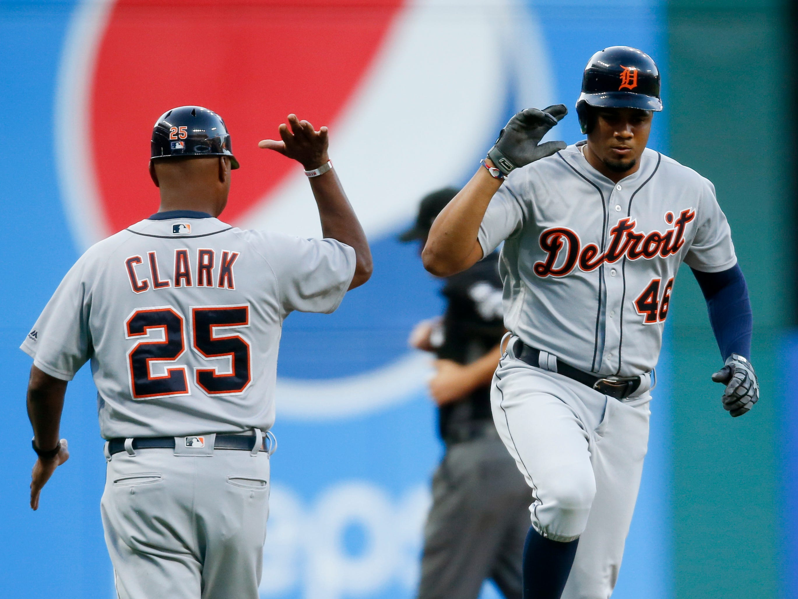 Detroit Tigers' Jeimer Candelario (46) celebrates with third base coach Dave Clark (25) after hitting a solo home run off Cleveland Indians starting pitcher Josh Tomlin during the first inning of a baseball game, Friday, Sept. 14, 2018, in Cleveland.