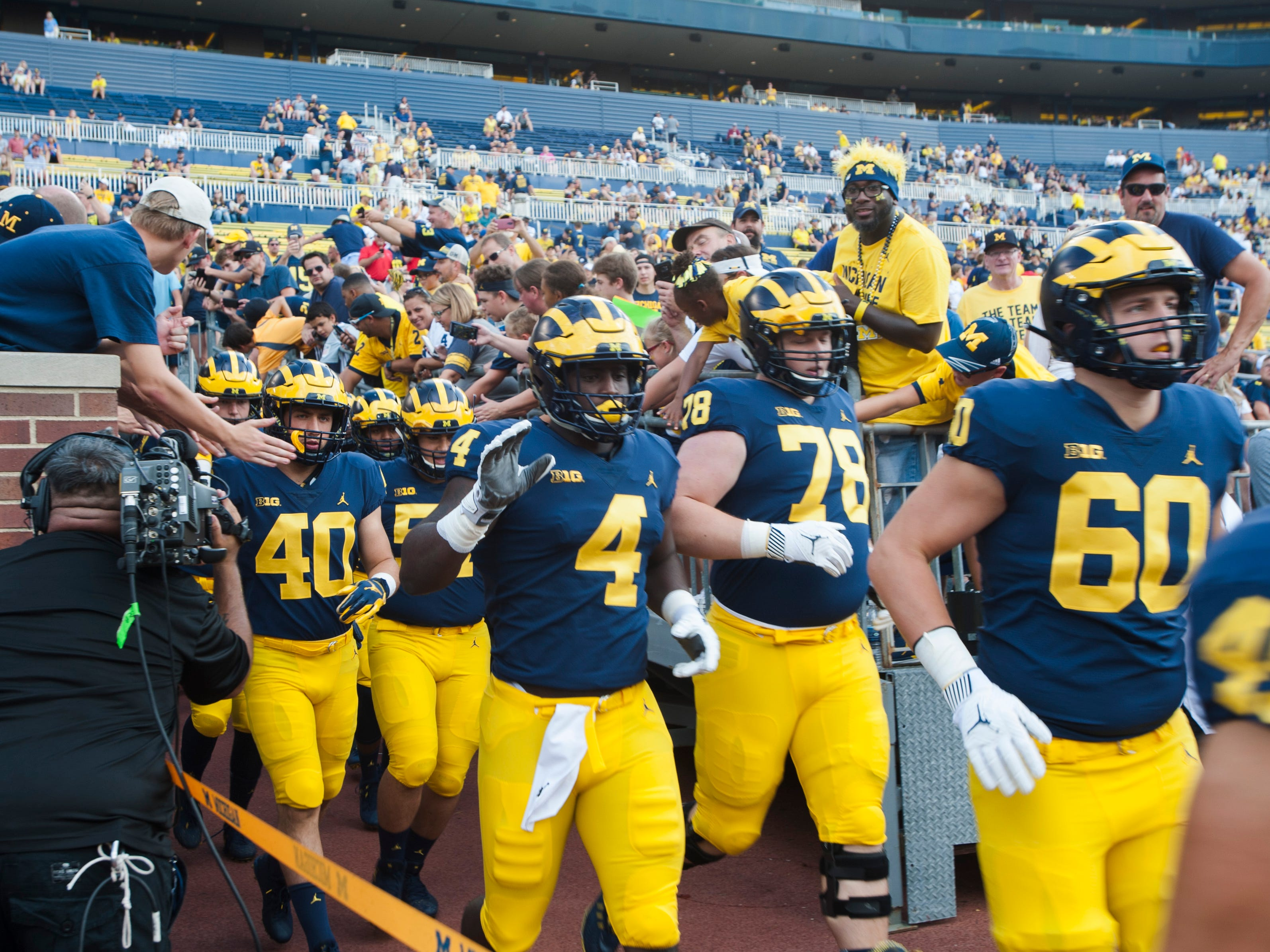 Michigan defensive players (from left) linebacker Ryan Nelson (40), defensive lineman Reuben Jones (4), Michigan offensive lineman Griffin Korican (78) and tight end Ryan Hayes (60) jog out of the Michigan Stadium tunnel for pre-game warmups before facing SMU Saturday, September 15, 2018.