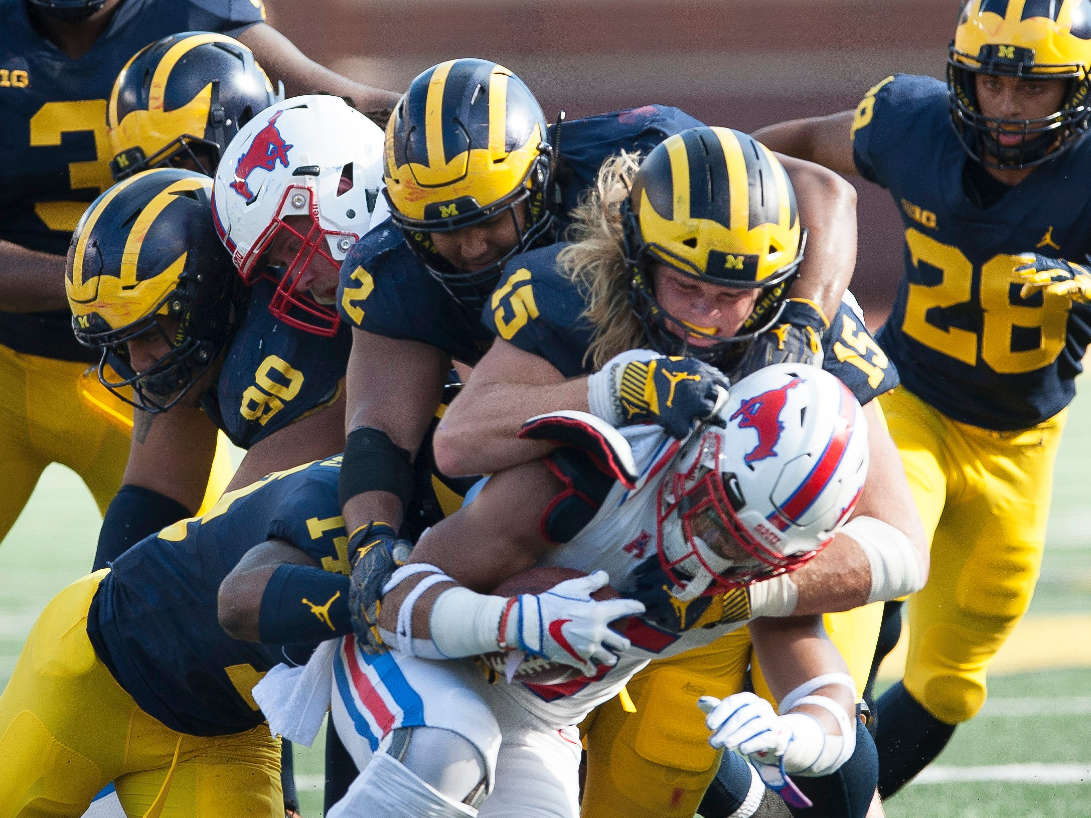 Michigan defensive lineman Chase Winovich (15) and a host of other Michigan defenders gang tackle Southern Methodist running back Xavier Jones for a loss in the second quarter. The other Michigan players are defensive back Josh Metellus (14), defensive lineman Bryan Mone (90) and defensive lineman Carlo Kemp (2).