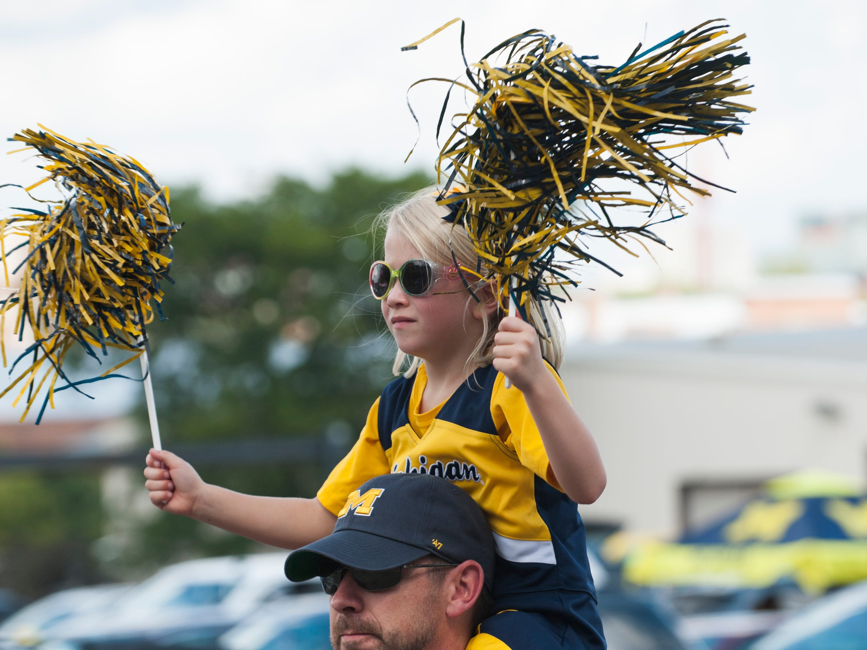 Six-year-old Lilly Neboyskey of Temperance, Mich. waves her maize and blue pom poms while riding atop her father Stefan Neboyskey's shoulders as they arrive at Michigan Stadium before the game.