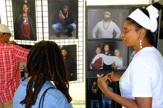 Phyllis Hubbard, director of the Campaign for Black Male Achievement health and healing strategies, right, shares stories about powerful portraits displayed on Saturday with Myett Risker.