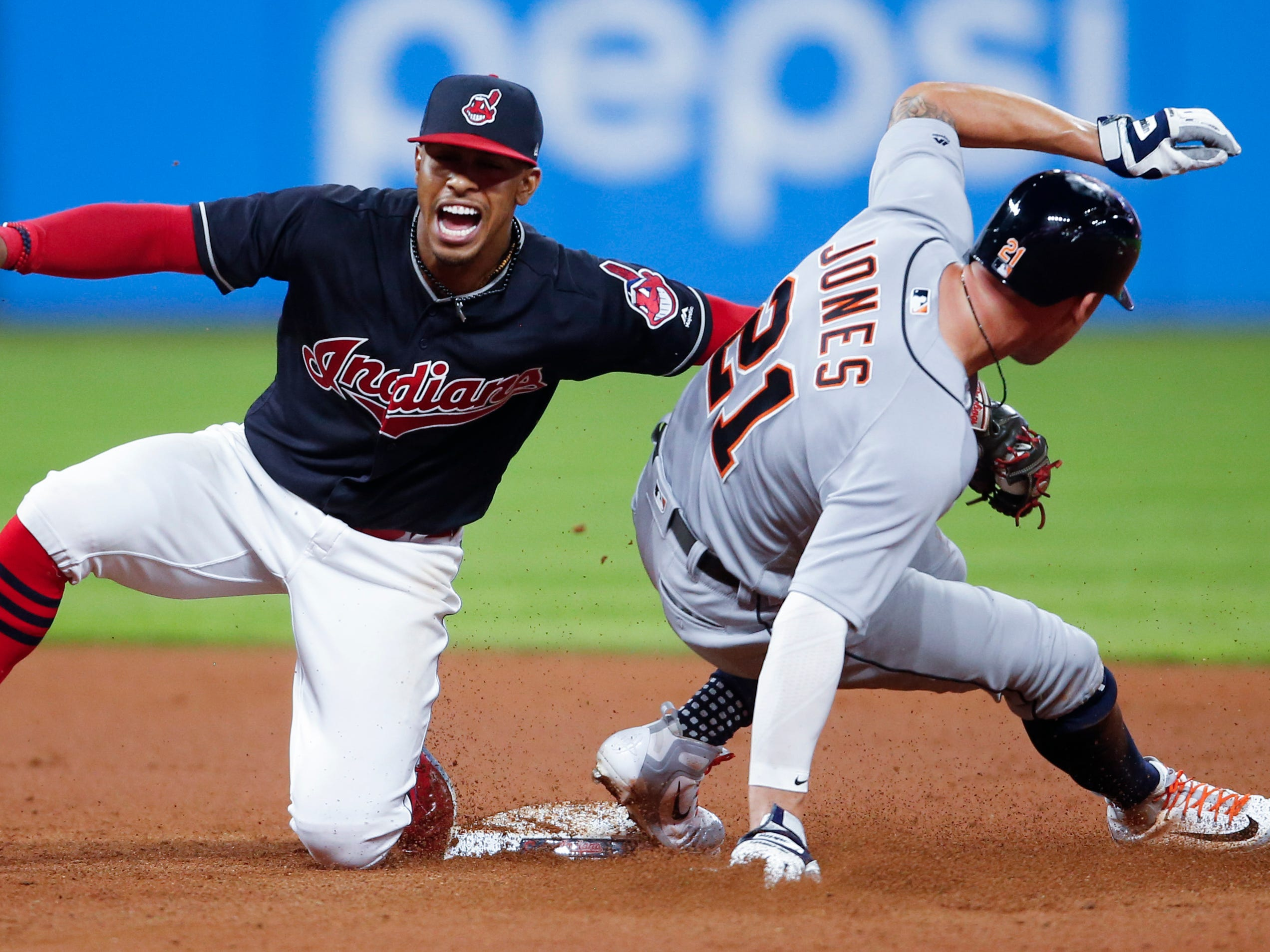 Detroit Tigers' JaCoby Jones, right, steals second base as Cleveland Indians' Francisco Lindor attempts a tag during the eighth inning.
