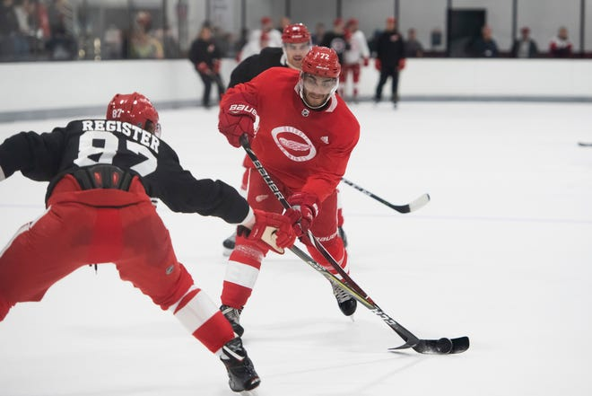 Detroit forward Andreas Athanasiou tries to shoot the puck past Detroit defenseman Matt Register during practice.
