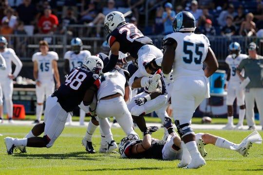 Rhode Island quarterback JaJuan Lawson is sacked by Connecticut Huskies Darrian Beavers (43), Kevon Jones (48) and Eli Thomas (22) in the second half at Pratt & Whitney Stadium at Rentschler Field on Sept. 15.