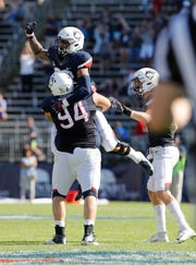 Eli Thomas celebrates with defensive lineman Kevin Murphy (94) after sacking Rhode Island quarterback JaJuan Lawson to end the game Sept. 15 at Pratt & Whitney Stadium at Rentschler Field.