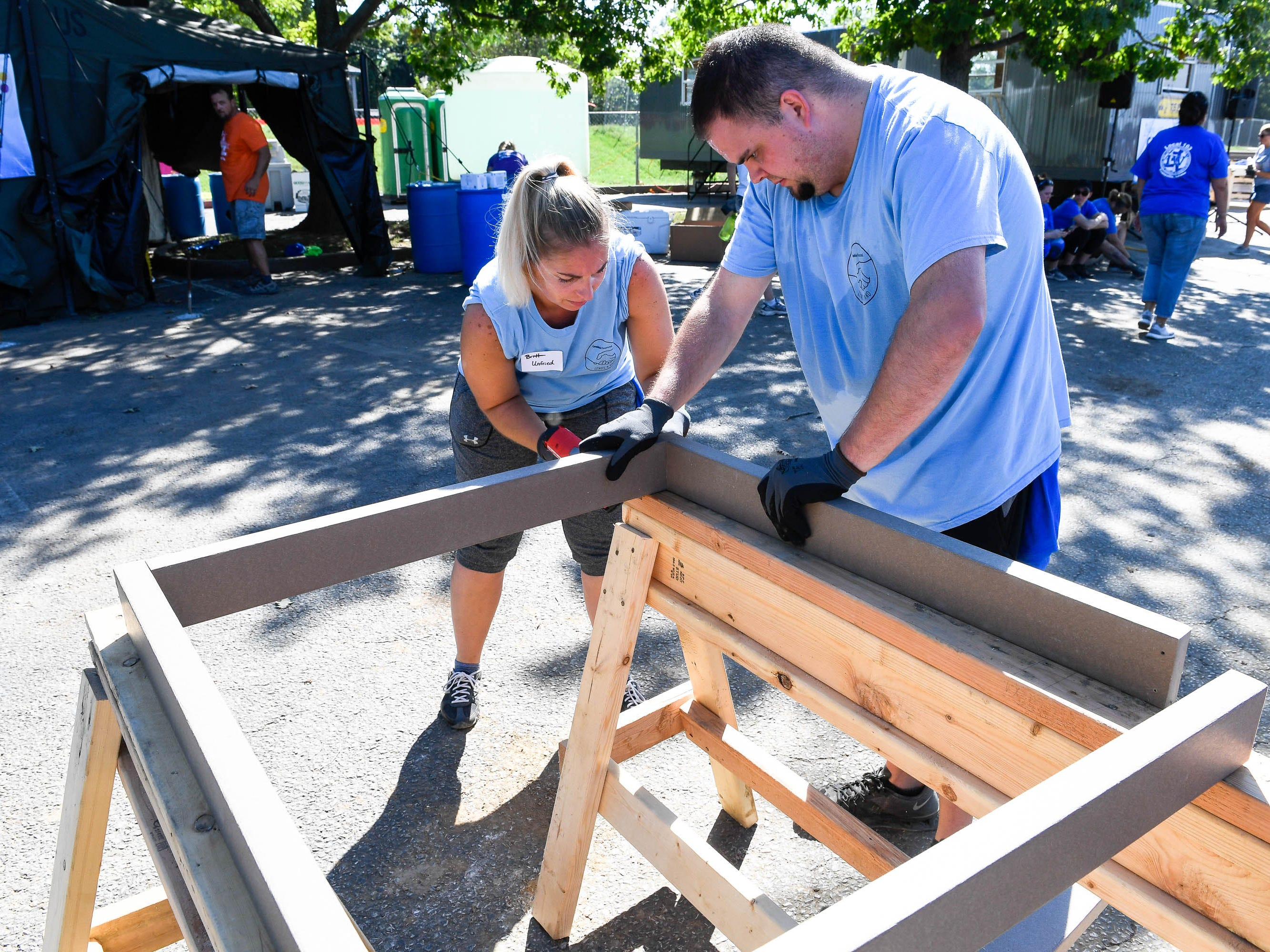 Britt Unfried and Josh Kolley screw together a composite wood frame as dozens of volunteers swarm over the Mickey's Kingdom playground under construction on the Evansville riverfront Friday, September 14, 2018.