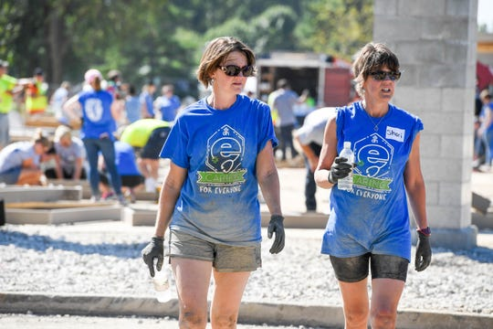Sisters Traci Robinson, left, with Deaconess, and Shari Thread with AstraZeneca, look for a shady spot to rehydrate after digging out post holes as dozens of volunteers swarm over the Mickey's Kingdom playground under construction on the Evansville riverfront Friday, September 14, 2018.