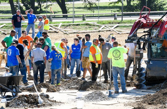 Dozens of volunteers swarm over the Mickey's Kingdom playground under construction on the Evansville riverfront Friday, September 14, 2018.