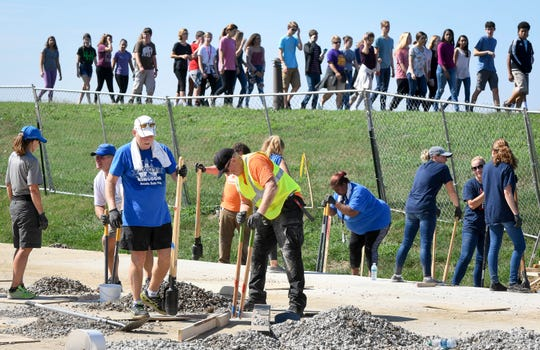 Signature School students get a look at the volunteers at work on Mickey's Kingdom playground under construction on the Evansville riverfront, students from the school plan on helping with the project Friday, September 14, 2018.