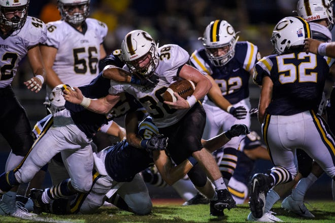 Central's Brennan Schutte (38) is tackled by Castle's Nyles Sutton (58) during the second quarter at John Lidy Field in Newburgh, Ind., Friday, Sept. 14, 2018.