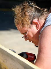 Melissa Lucas with Wal-Mart shoots some screws in to a 2x4 frame as dozens of volunteers swarm over the Mickey's Kingdom playground under construction on the Evansville riverfront Friday, September 14, 2018.