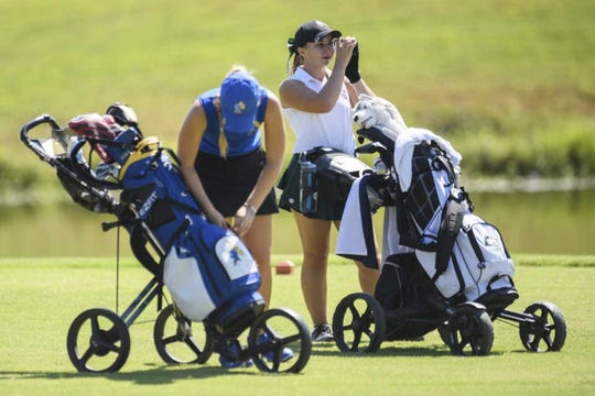 North senior Katelyn Skinner uses a range finder to judge the distance on her tee shot. The Huskies won the sectional with a 288