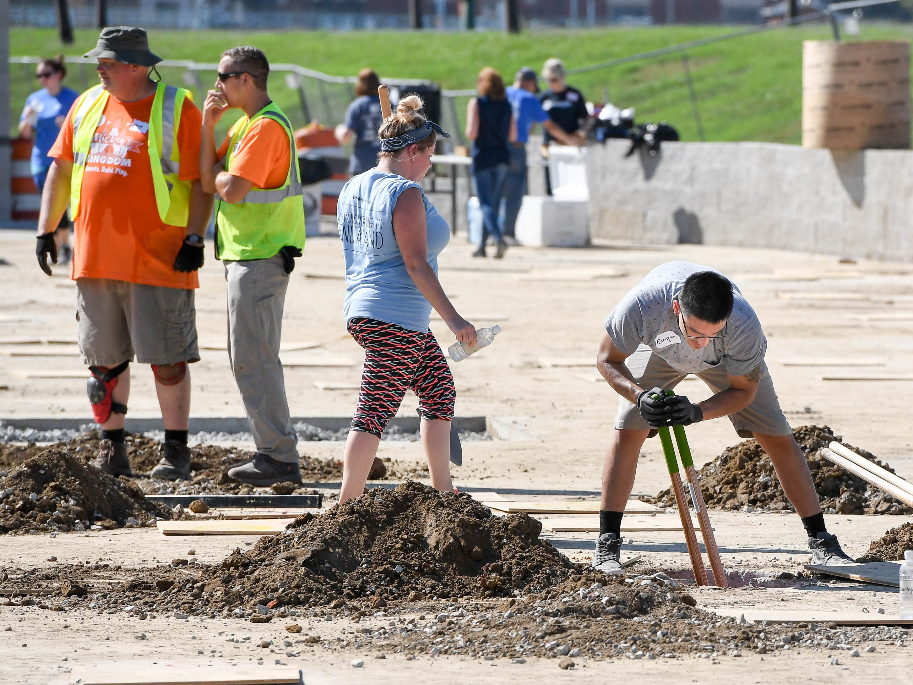 Enrique Alvarez with One Main Financial, righty, helps dig post holes as dozens of volunteers swarm over the Mickey's Kingdom playground under construction on the Evansville riverfront Friday, September 14, 2018.