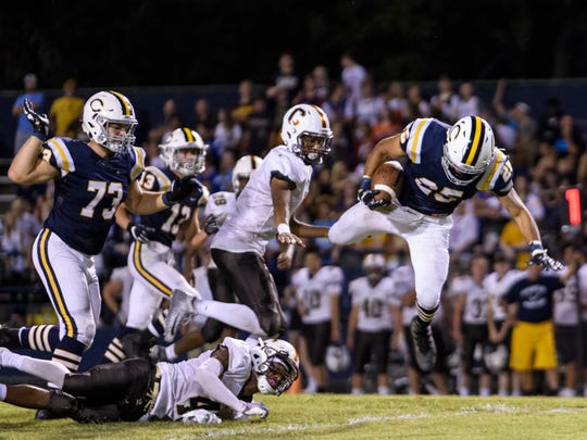 Castle's Noah Taylor (25) flies over Central's Malcolm Depriest (4) before catching his balance to make a first down at John Lidy Field in Newburgh, Ind., Friday, Sept. 14, 2018. The Bears remain undefeated – with a 5-0 record – after defeating the Knights, 41-34.