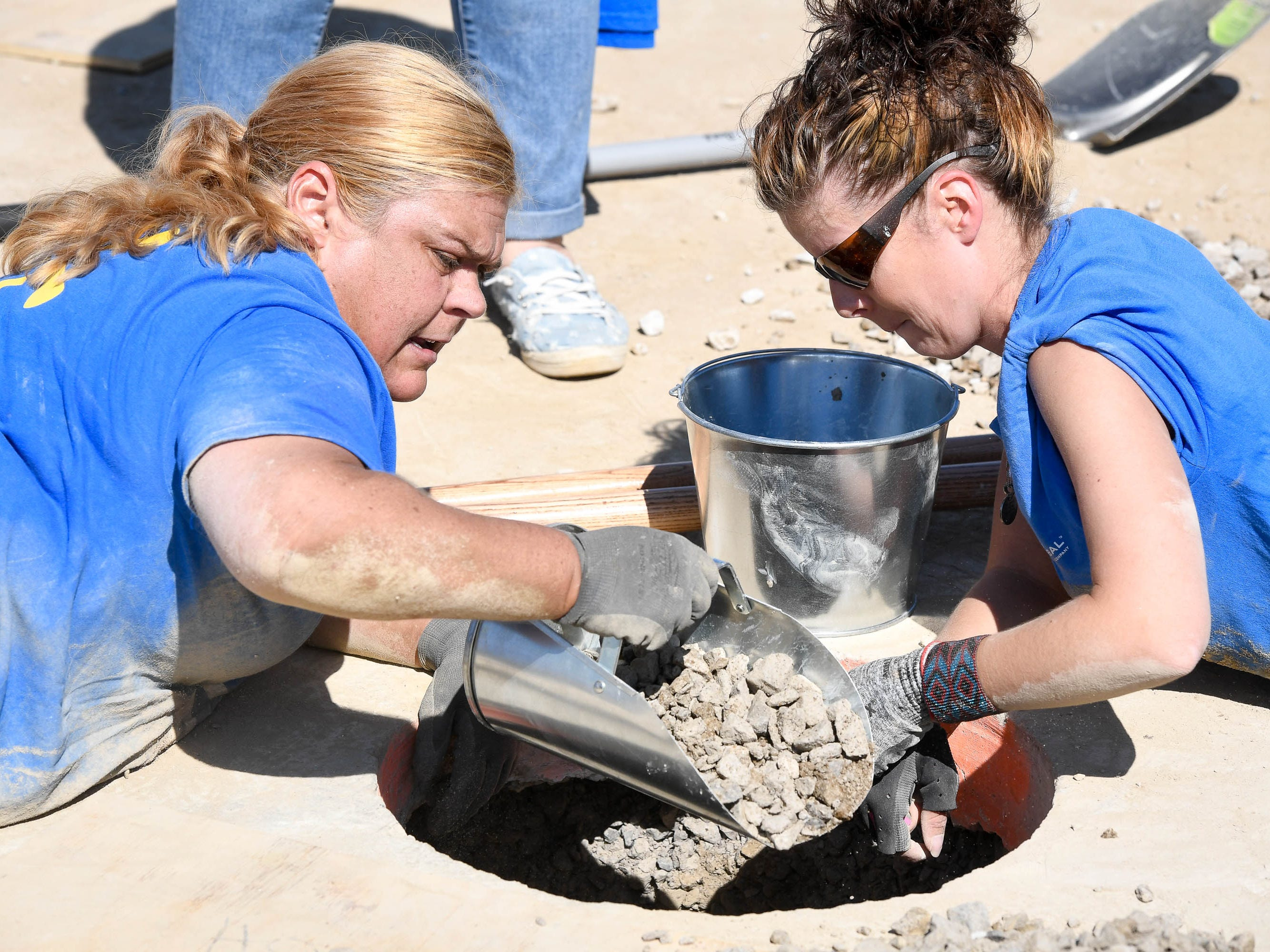 Volunteers Stephanie Henderson, left, with Wal-Mart and Britney Parton, with SRG Global, clean gravel out of one of the post holes as dozens of volunteers swarm over the Mickey's Kingdom playground under construction on the Evansville riverfront Friday, September 14, 2018.