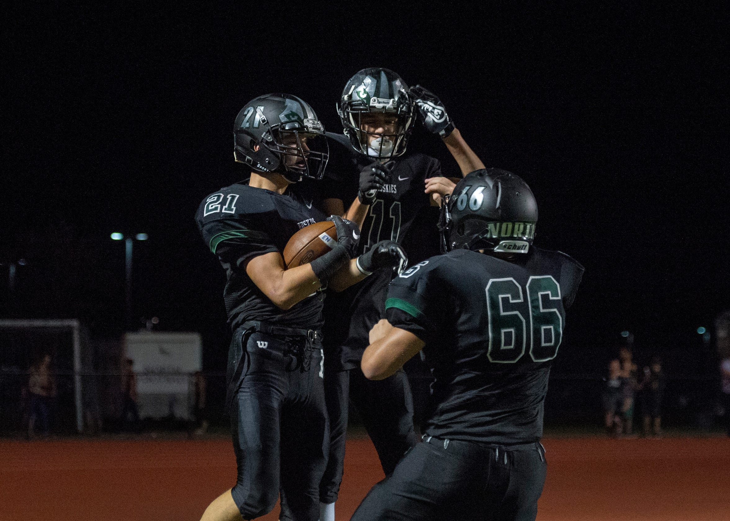 North's Dylan Mckinney (21), Seth Seniour (11) and Kyle Draper (66) celebrate after a touchdown during the North vs Mater Dei game at Bundrant Stadium on Friday, Sept. 14, 2018.