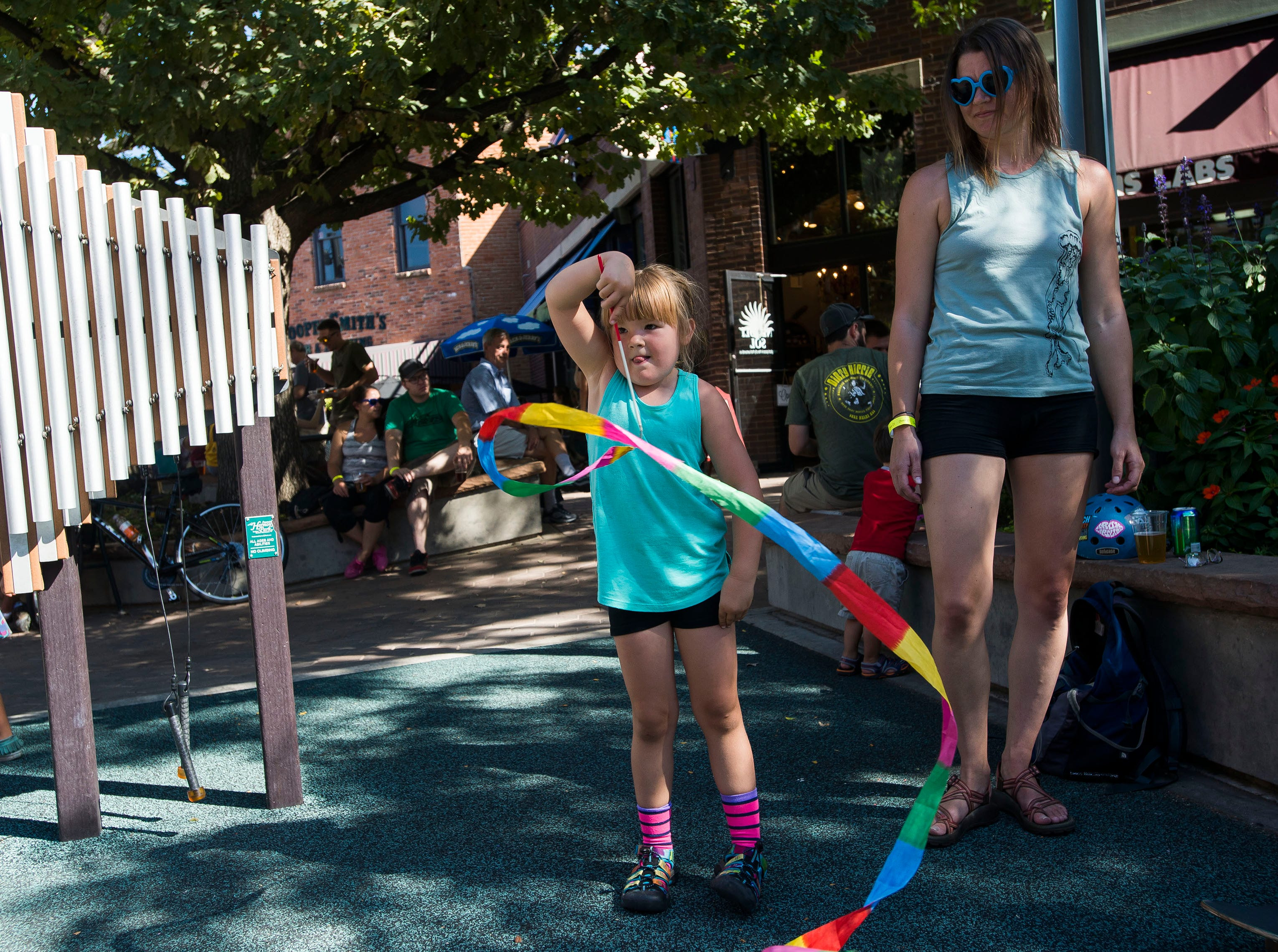 Maya McGowan twirls her ribbon while her mother Liz Brandon looks on during Fortoberfest 2018 on Saturday, Sept. 15, 2018, at Old Town Square in Fort Collins, Colo.