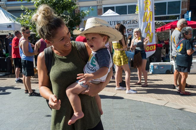 Jamie Miller dances with one-year-old Wilde Miller while The Symbols perform on the Choice Organics stage during Fortoberfest 2018 on Saturday, Sept. 15, 2018, at Old Town Square in Fort Collins, Colo.