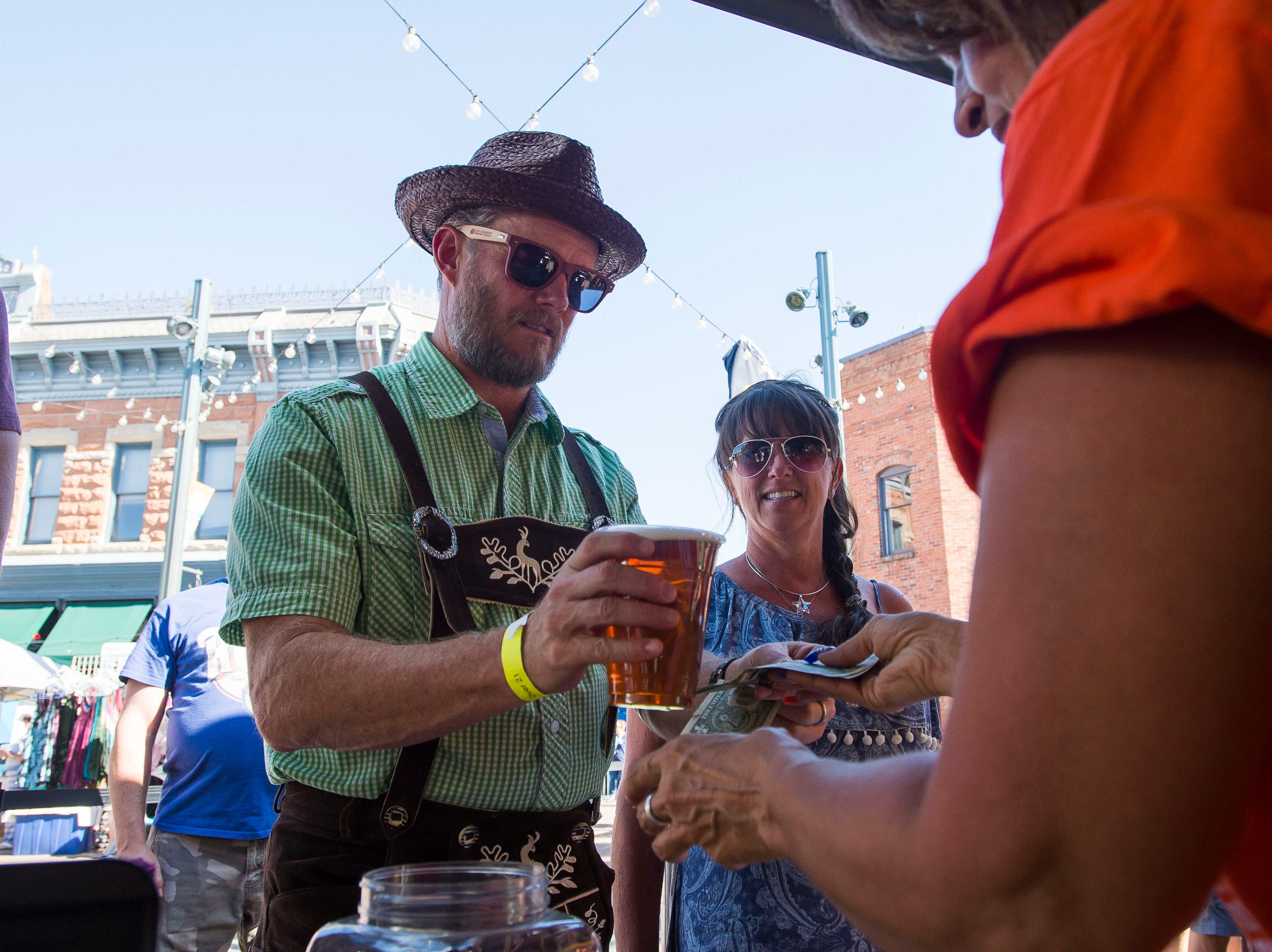 Volunteer Elaine Stewart, right, hands Mike Patterson a beer while Elisabeth Patterson waits on her wine during Fortoberfest 2018 on Saturday, Sept. 15, 2018, at Old Town Square in Fort Collins, Colo.