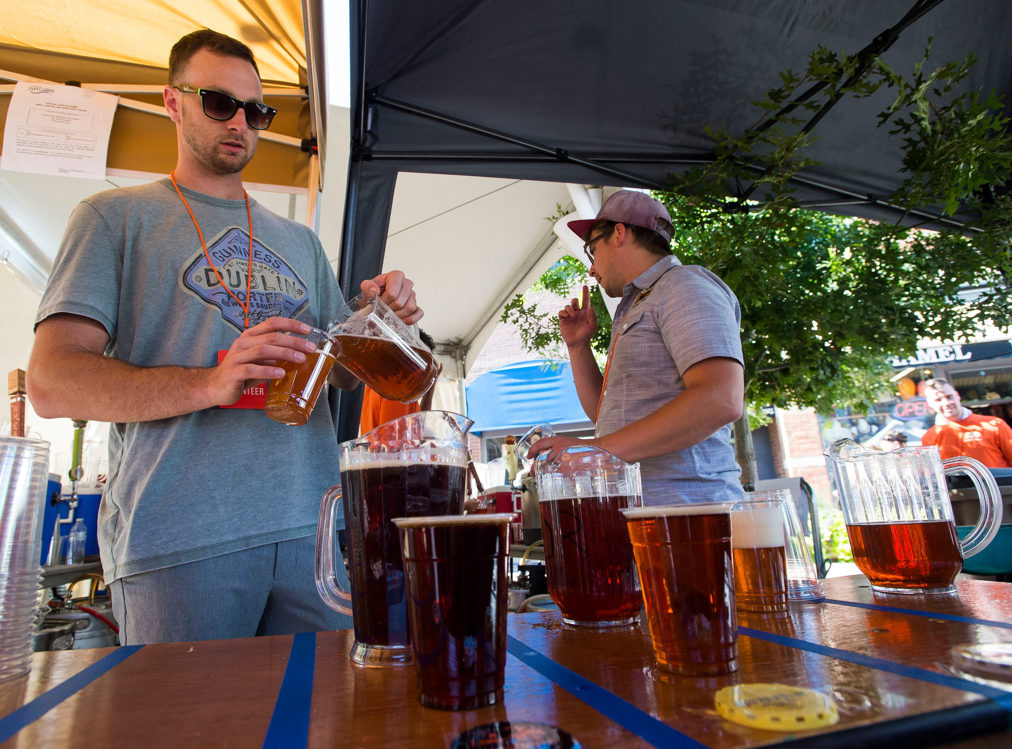 Volunteer Evan Raiskin pours beers for patron during Fortoberfest 2018 on Saturday, Sept. 15, 2018, at Old Town Square in Fort Collins, Colo.