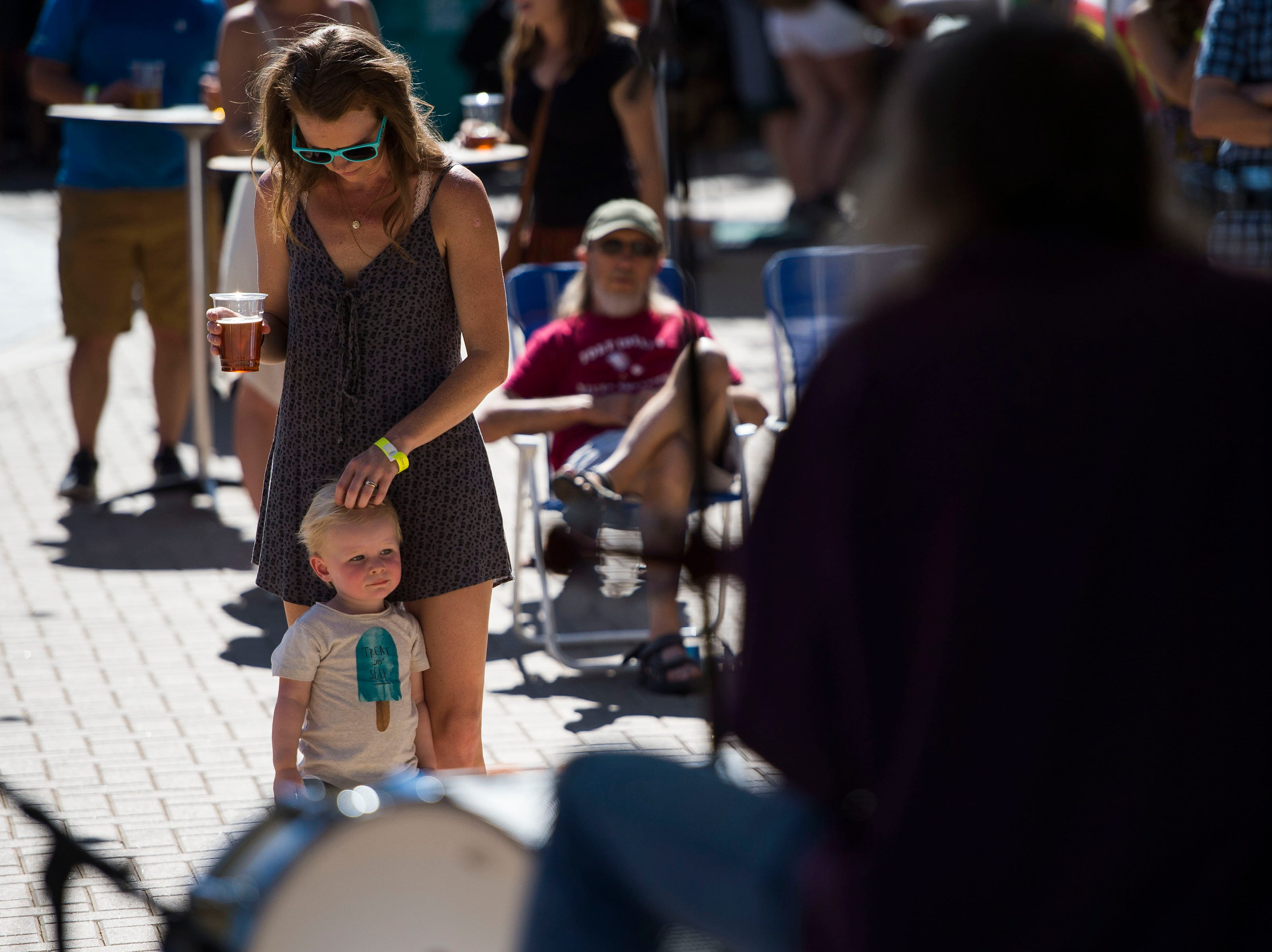 Landis Trainor keeps an eye on Riggins, 1, while he keeps an eye on The Symbols, performing on the Choice Organics stage during Fortoberfest 2018 on Saturday, Sept. 15, 2018, at Old Town Square in Fort Collins, Colo.