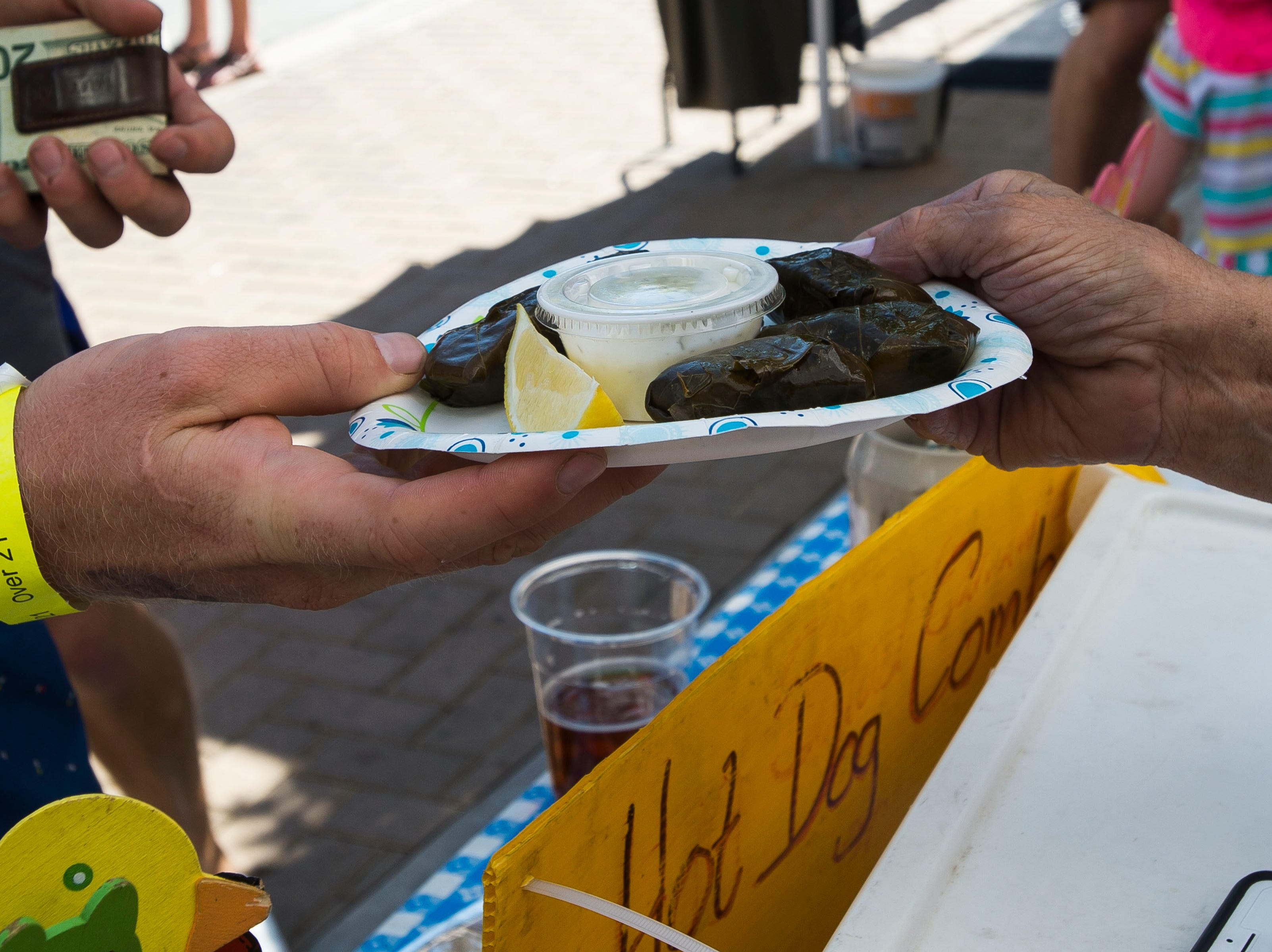 Robbie Boettger gets a plate of stuffed olive leaves from Gunter's Bavarian Grill during Fortoberfest 2018 on Saturday, Sept. 15, 2018, at Old Town Square in Fort Collins, Colo.