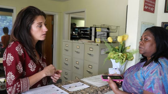 Mary Wilson of Realty Services, left, explains how Section 8 vouchers work to Jones Walker resident Ebony Lee, who hopes to be getting one soon. The City of Fort Myers is lobbying HUD to cancel its contract with the owner of the aging, privately owned affordable apartment complex so residents can get their own housing vouchers and move.