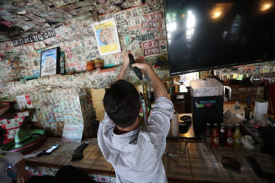 James Pyles of Fort Myers adds a dollar to the wall at Cantina Captiva. He and his co-workers stopped in after work and added their dollar to the wall.  Saturday, some of the famous dollar bills that line Cantina Captiva's walls were pulled off for island workers in need. And throughout the weekend, residents responded to a social media campaign: Help Bring the Green Back to Sanibel & Captiva by spending their money at local establishments.
