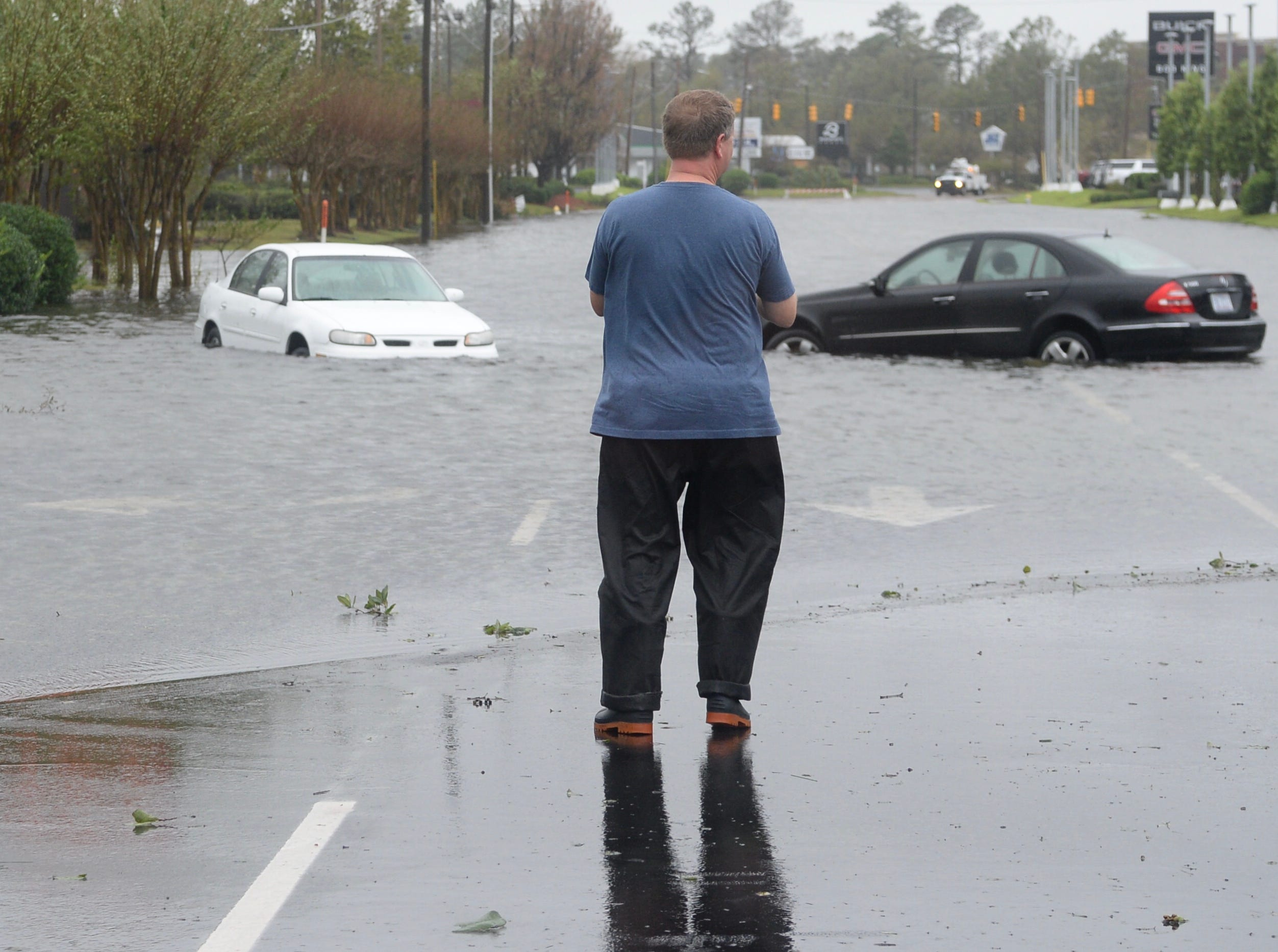 A resident looks at a flooded street in Wilmington, N.C., on Saturday, Sept. 15, 2018.