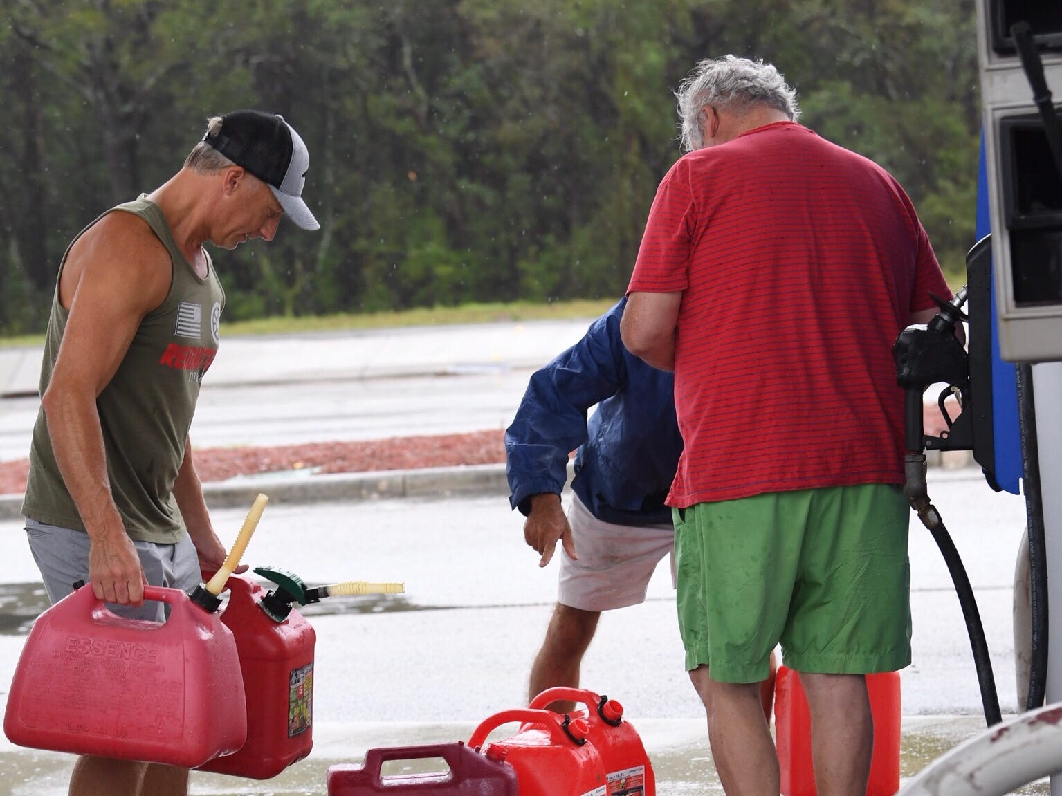 Blair Young, left, takes his gas containers back to his truck from Candy's Exxon in Wilmington on Saturday, Sept. 15, 2018.