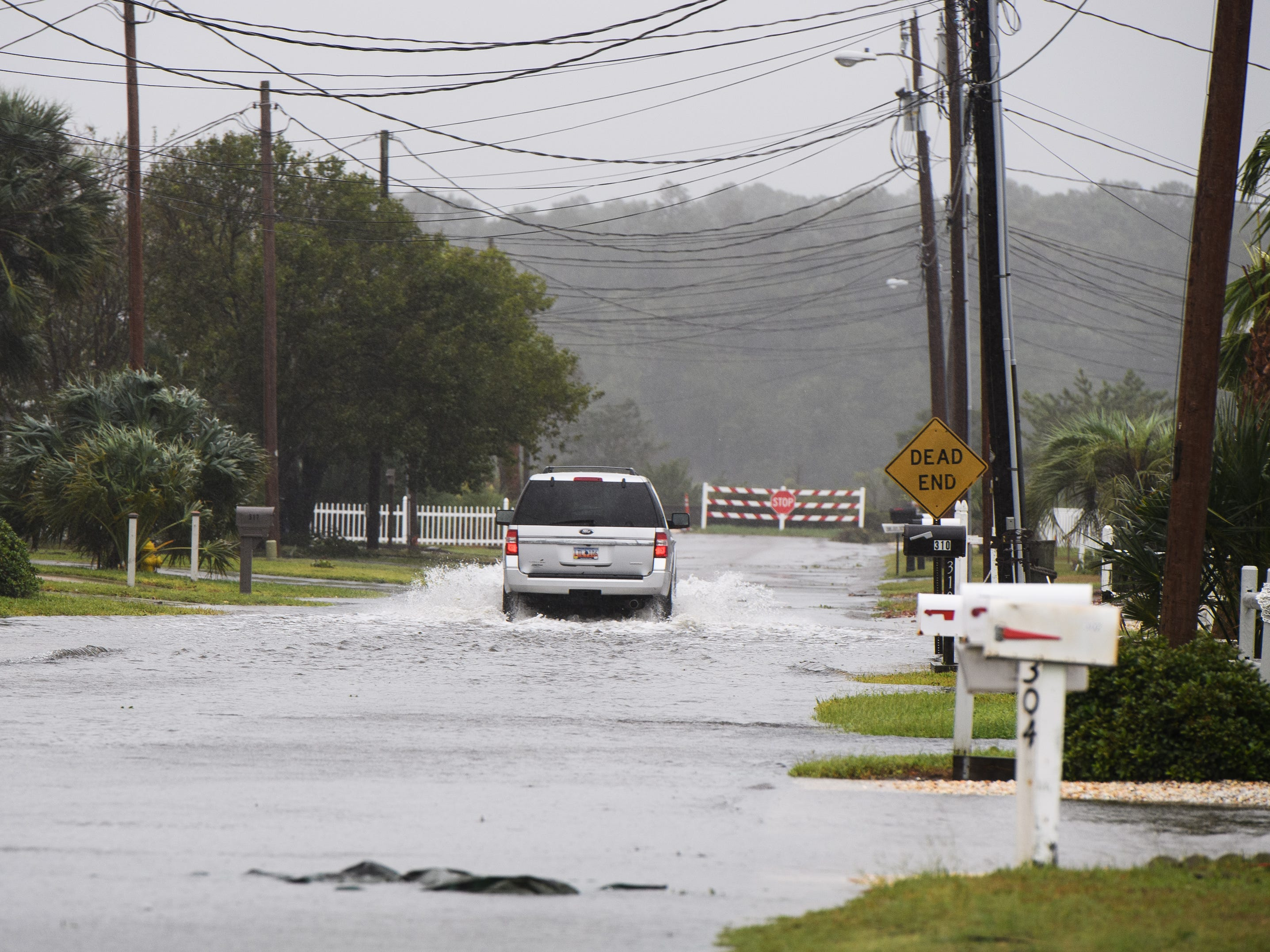 A motorist drives through a flooded residential road in North Myrtle Beach on Saturday, Sept. 15, 2018.