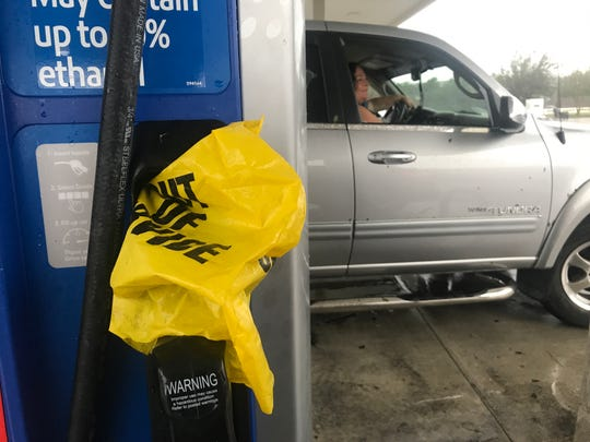 "Ann Blake sits in her car after she said a person told her, ""no power, no gas, get lost"" at Candy's Exxon in Wilmington, N.C. on Saturday, Sept. 15, 2018."