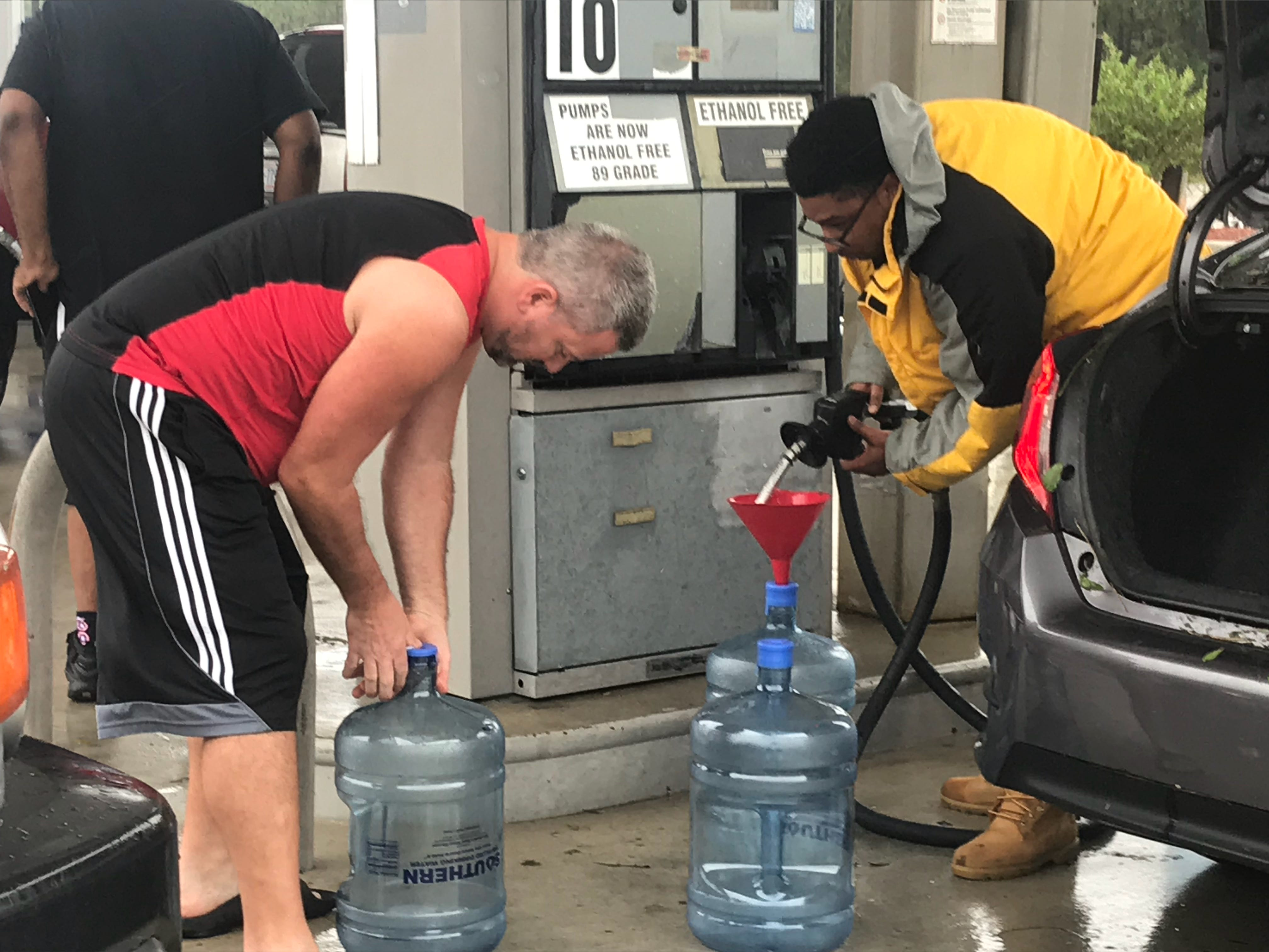 Two men fill water coolers with fuel at Candy's Exxon in Wilmington on Saturday, Sept. 15, 2018.