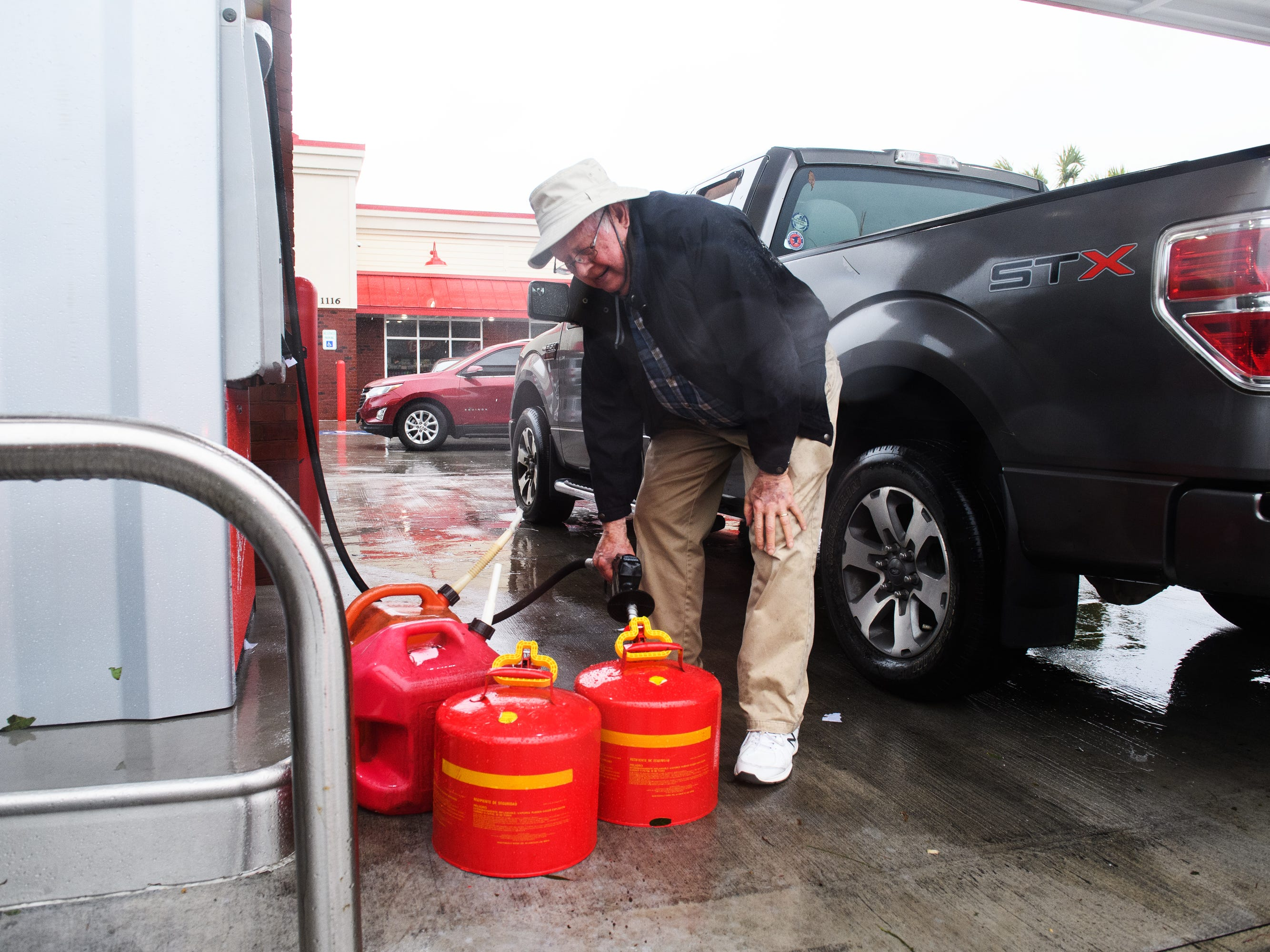Bill West of Little River fills up his gas cans at Boulineau's Corner in North Myrtle Beach on Saturday, Sept. 15, 2018.