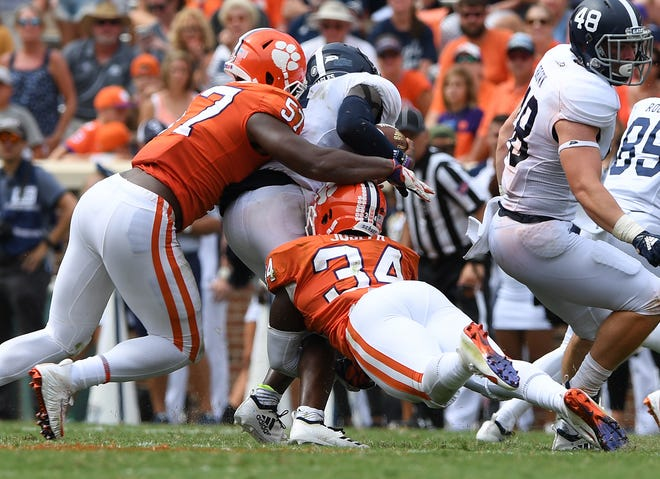 Clemson linebackers Tre Lamar (57), left, and Kendall Joseph (34) bring down Georgia Southern quarterback Shai Werts (4) during the 4th quarter Saturday, September 15, 2018, at Clemson's Memorial Stadium.