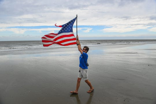 9/14/18 3:43:41 PM -- Isle of Palms, SC, U.S.A  -- Mason Moise, 18, from Charleston, SC carries a U.S. flag in the increasing winds on Isle of Palms Beach Friday afternoon prior to the arrival of Hurricane Florence.  --    Photo by Jack Gruber, USA TODAY staff