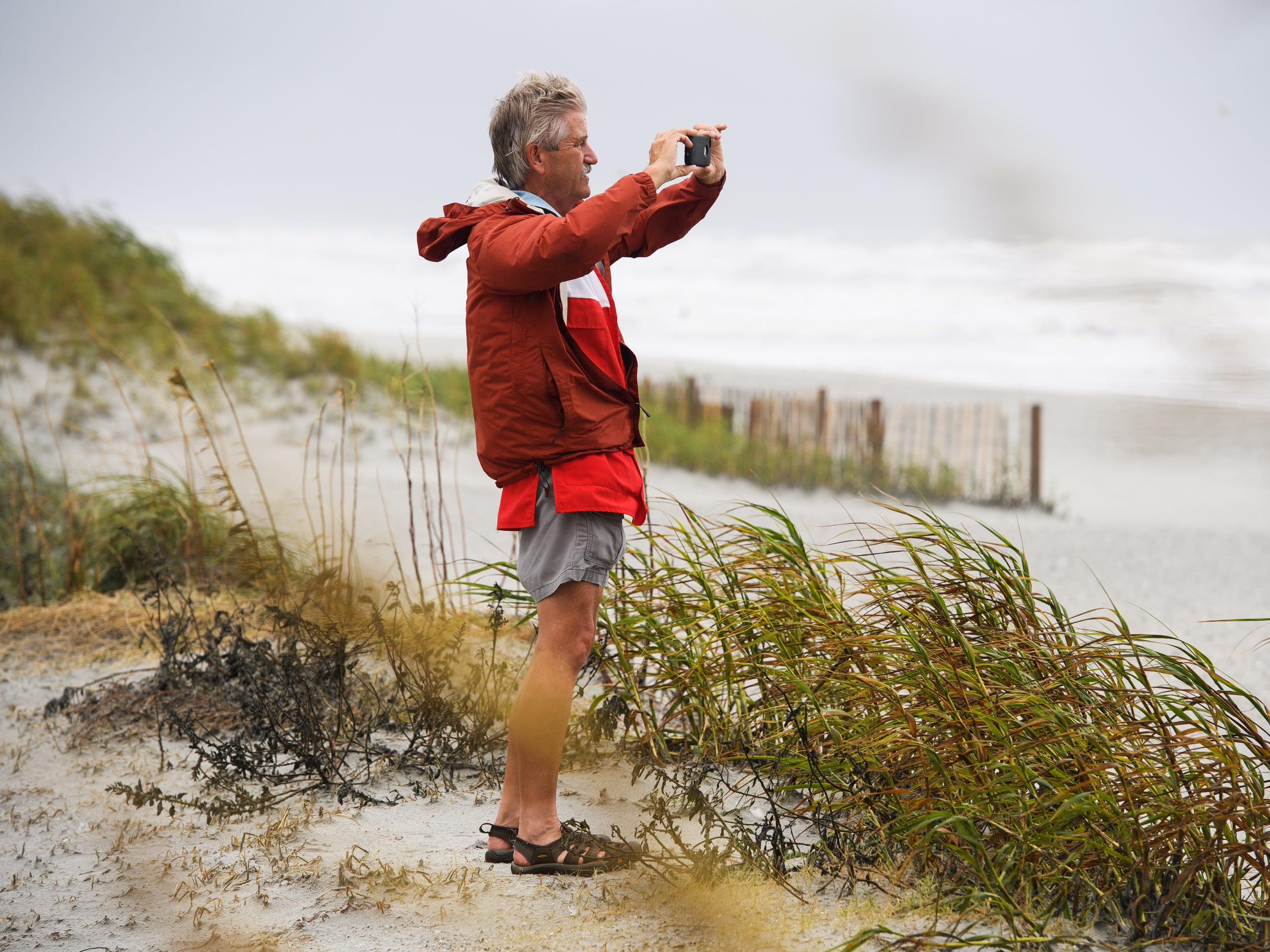 Chuck Billing, a volunteer with the Red Cross, takes a photo at the beach while the tide begins to rise in North Myrtle Beach on Saturday, Sept. 15, 2018.