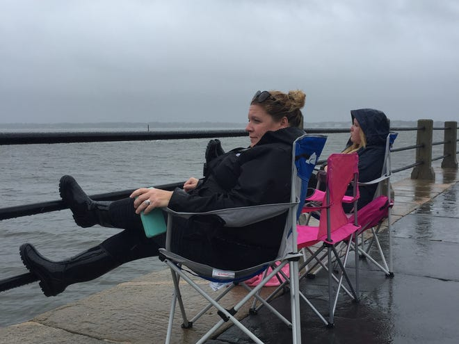 Julie Blackburn and her daughter Sophie sit along The Battery seawall and toward the Ravenel Bridge as Tropical Storm Florence brings rain and wind on September 15, 2018.
