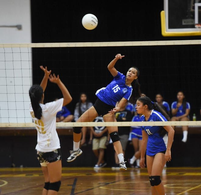 Notre Dame's Brianne Leon Guerrero (15) spikes the ball over the net against the George Washington Geckos during their IIAAG Girls' High School Volleyball game at the GW High School Gym on Sept. 15, 2018.