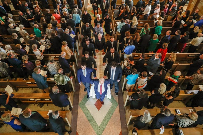 Pall bearers make their way out of the sanctuary with the casket during the Mass of Christian Burial for longtime public servant Mary Moriarty Adams, held at Little Flower Catholic Church in Indianapolis on Saturday, Sept. 15, 2018.