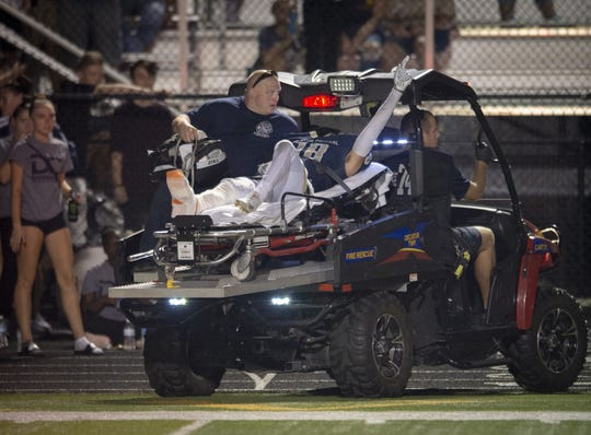 Decatur Central High School sophomore Peyton Horsley (18) signals to the crowd as they cheer for him while being taken off the field by medics following an apparent leg injury during the second half of action. Decatur Central High School hosted Mooresville High School in IHSAA varsity football action, Friday, Sept. 14, 2018. Decatur Central won 38-28.