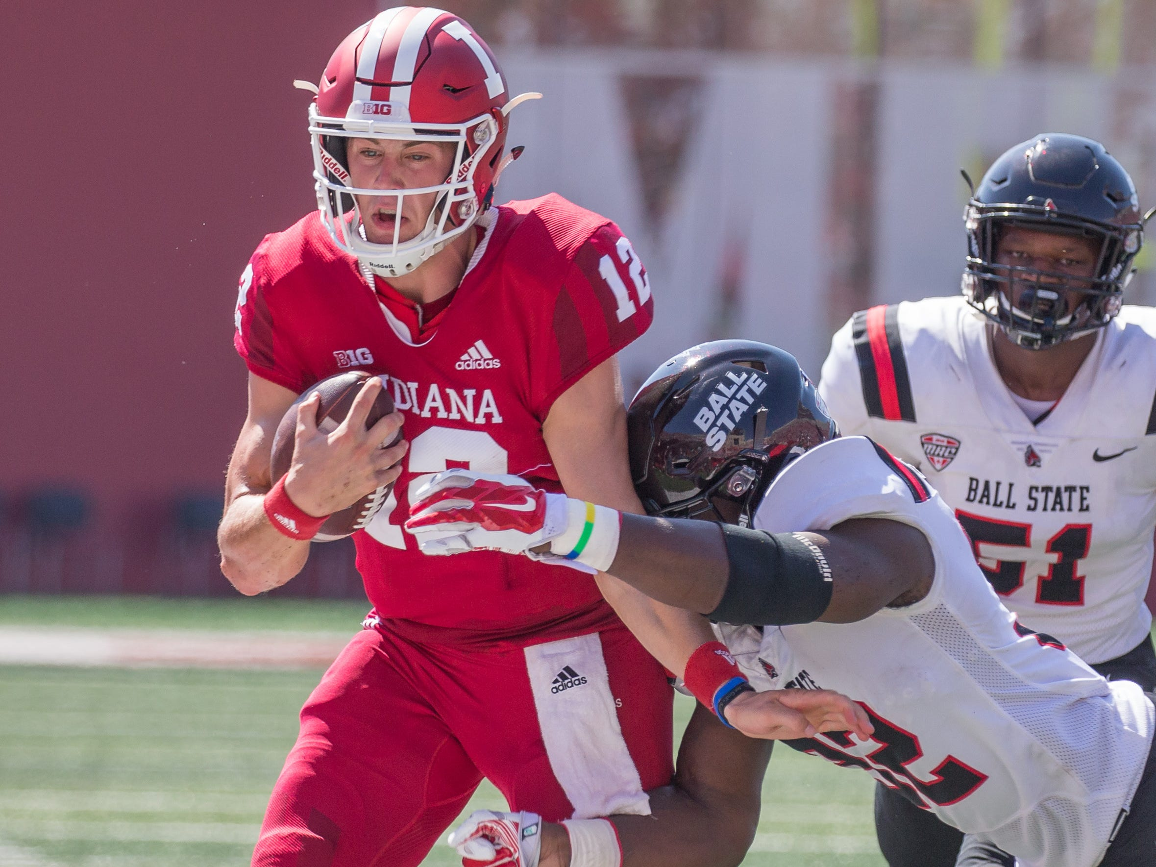 Indiana Hoosiers quarterback Peyton Ramsey (12) runs with the ball while Ball State Cardinals linebacker Jeremiah Jackson (32) tackles him in the first quarter at Memorial Stadium .