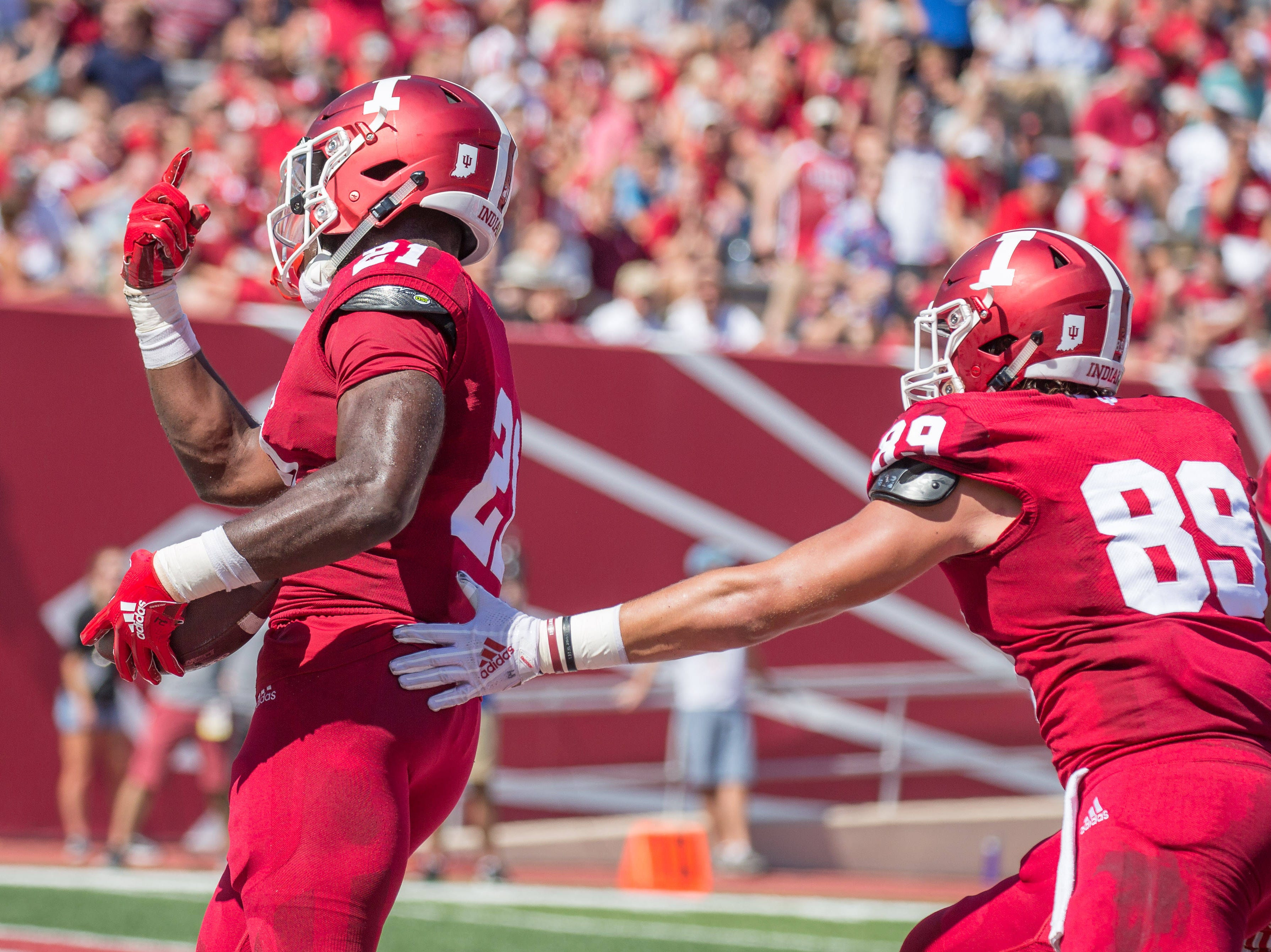 Indiana Hoosiers running back Stevie Scott (21) celebrates his touchdown with tight end Matt Bjorson (89) in the first quarter against the Ball State Cardinals at Memorial Stadium .