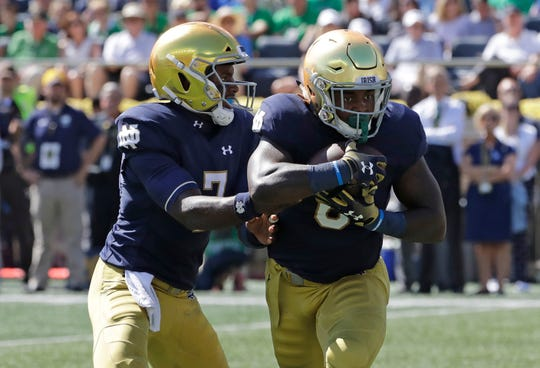 Notre Dame quarterback Brandon Wimbush, left, drops off the ball to running back Tony Jones Jr., during the first half of an NCAA college football game against Vanderbilt in South Bend, Ind., Saturday, Sept. 15, 2018.