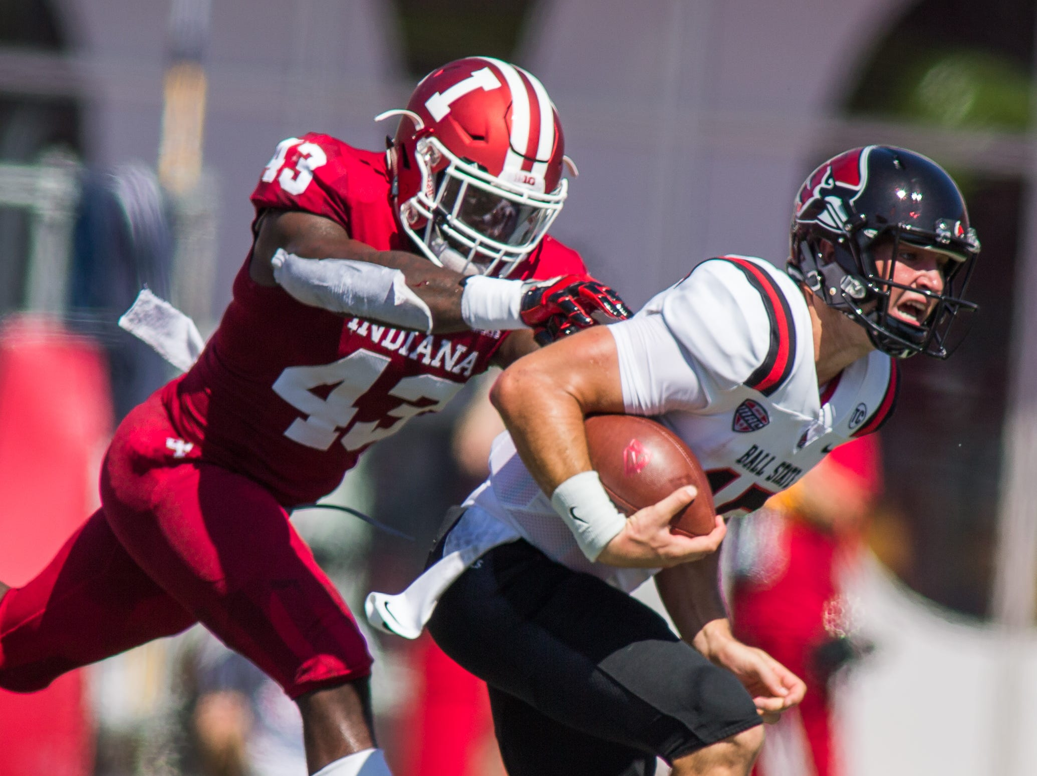 Ball State Cardinals quarterback Riley Neal (15) runs the ball and is tackled by IIndiana Hoosiers linebacker Dameon Willis Jr. (43) in the first quarter at Memorial Stadium .