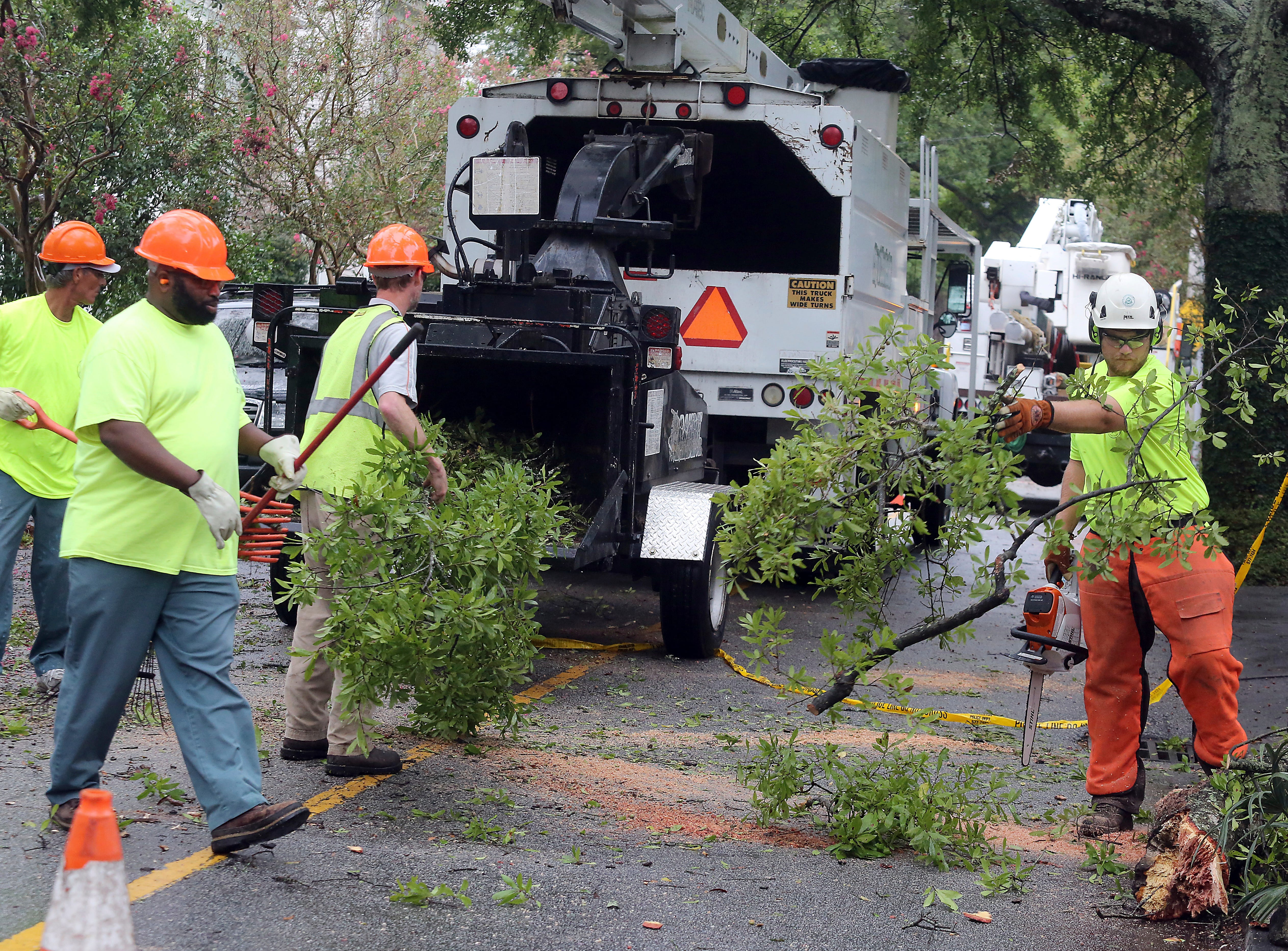 Charleston, N.C., forestry employees remove a large limb from New Street  near Broad Saturday, Sept.r 15, 2018, after it came down from tropical storm Florence.