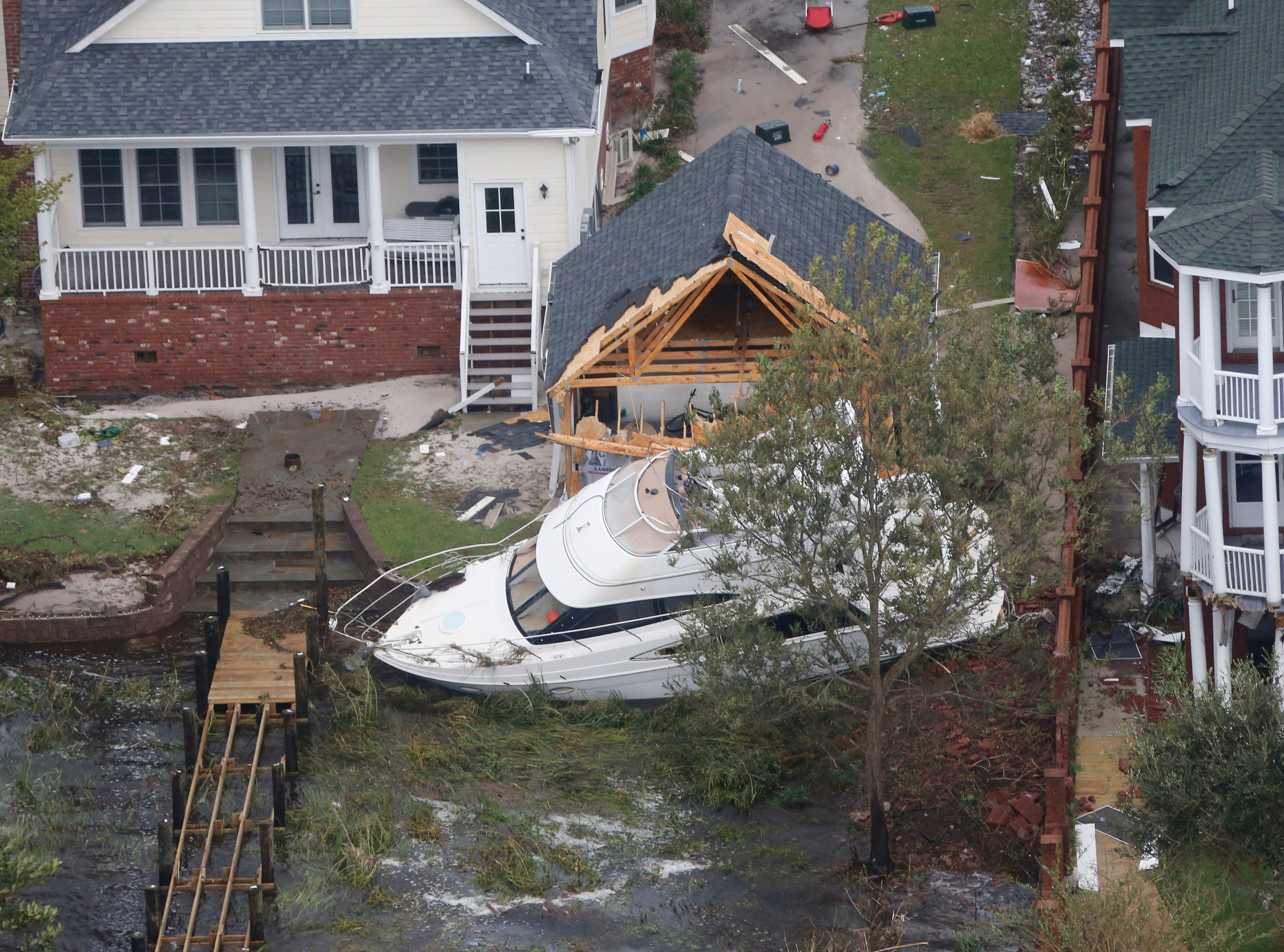 A yacht sits on the Neuse river bank in between buildings after hurricane Florence passed through the area in New Bern, NC., Saturday, Sept. 15, 2018.