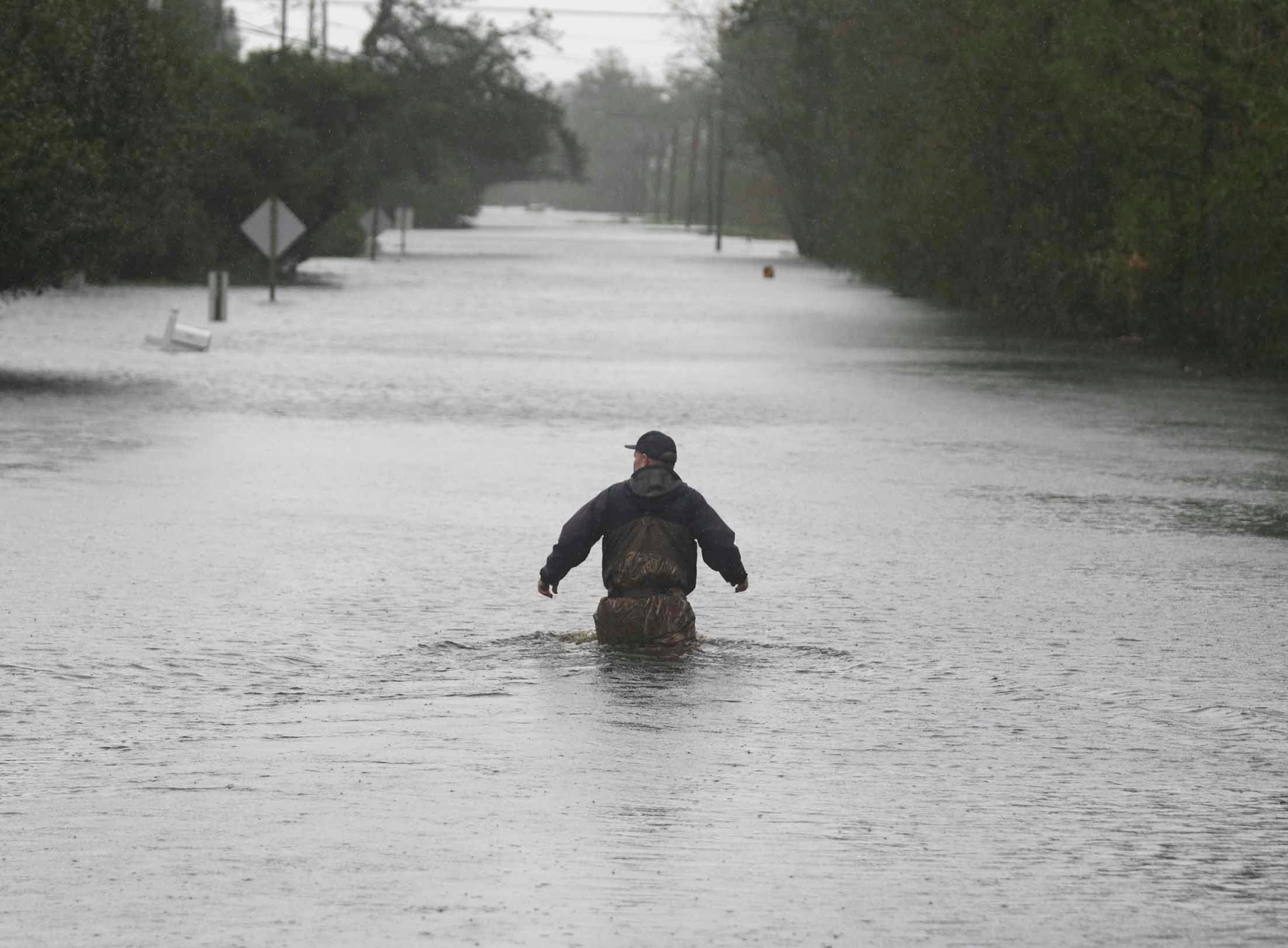 A member of the US Coast Guard walks down Mill Creek Road checking houses after tropical storm Florence hit Newport N.C., Saturday, Sept. 15, 2018. A day after blowing ashore with 90 mph (145 kph) winds, Florence practically parked itself over land all day long and poured on the rain.