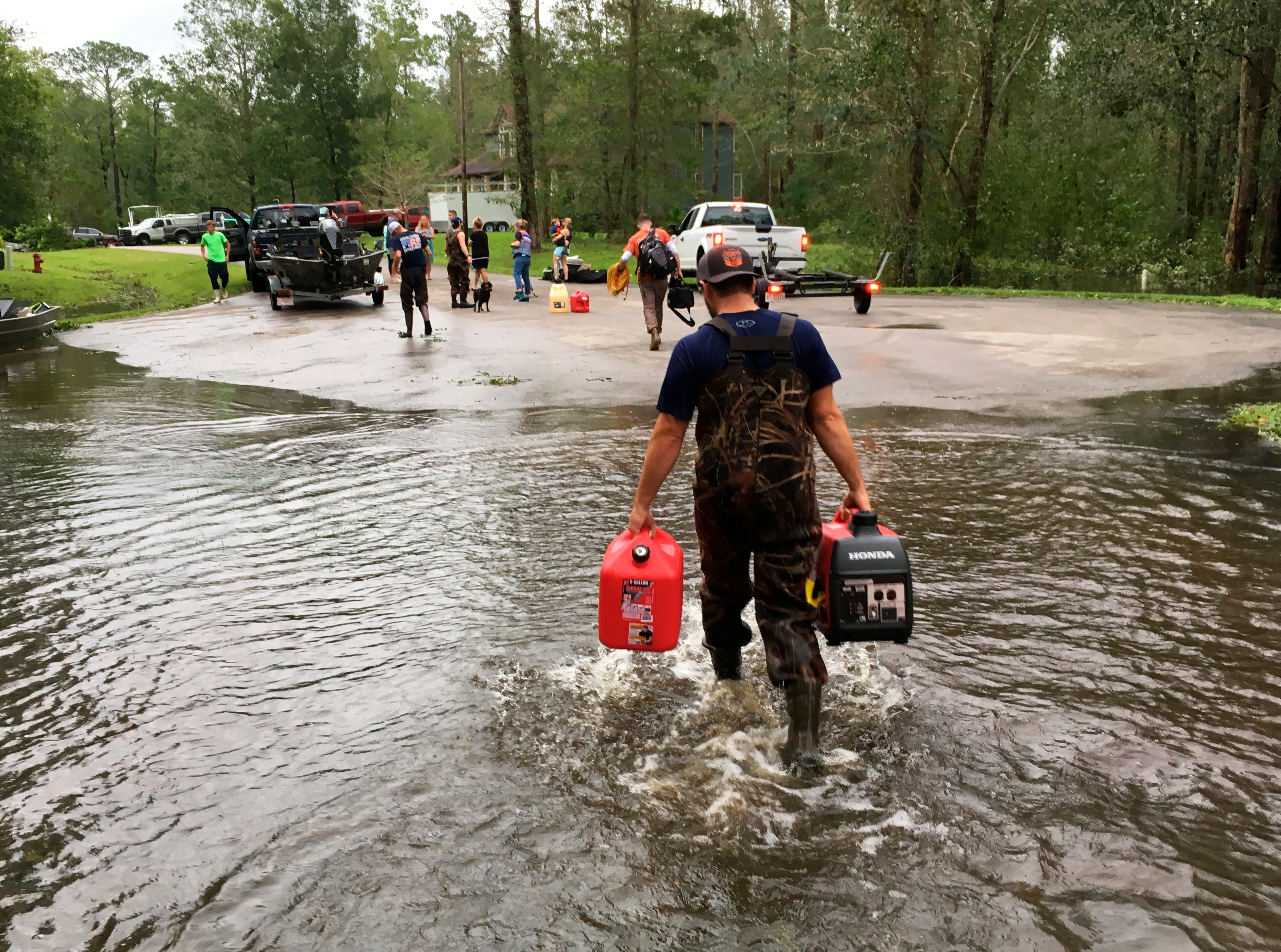 Kevin Knox carries gas and a generator after being rescued from his flooded neighborhood from the effects of Florence, now a tropical storm, in New Bern, N.C., on Saturday, Sept. 15, 2018.