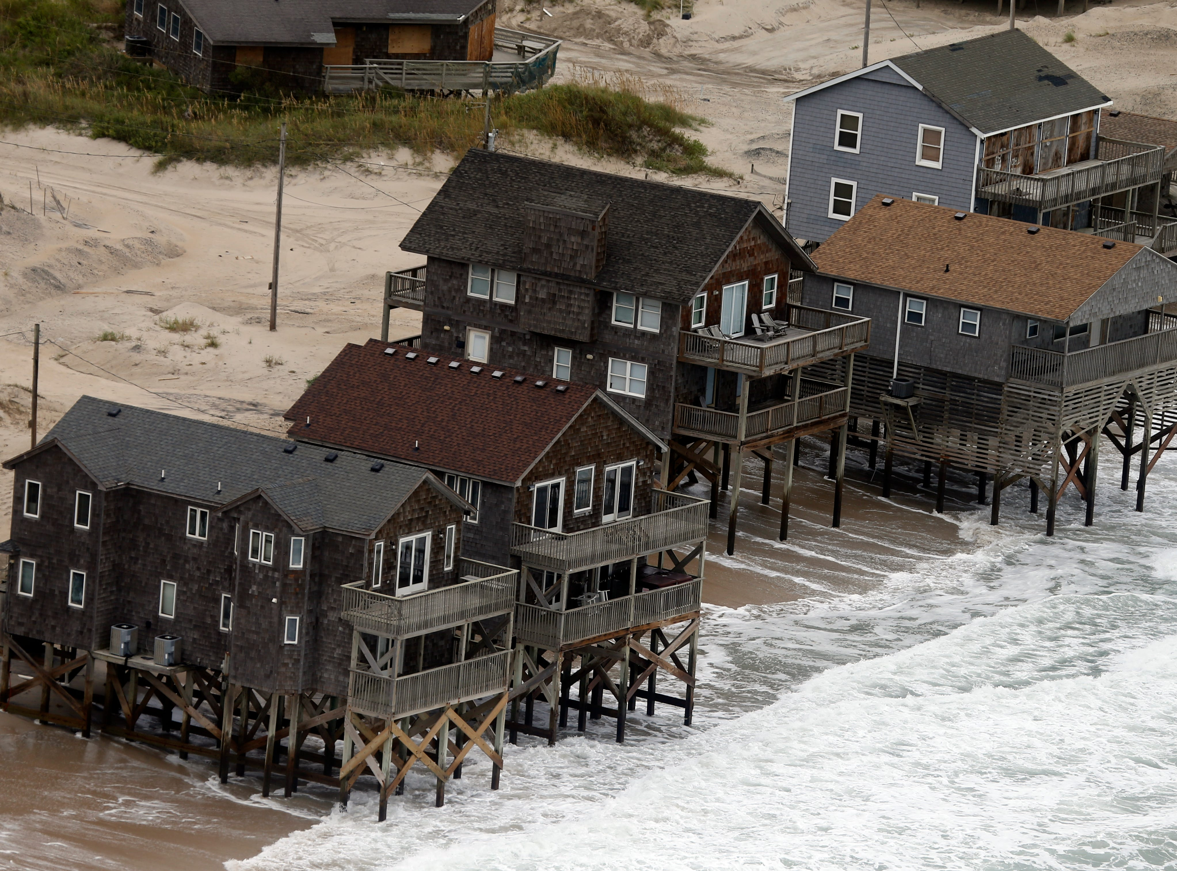 Oceanfront homes sit over the water as waves from hurricane Florence continue to pound the coast in Rodanthe NC., Saturday, Sept. 15, 2018.